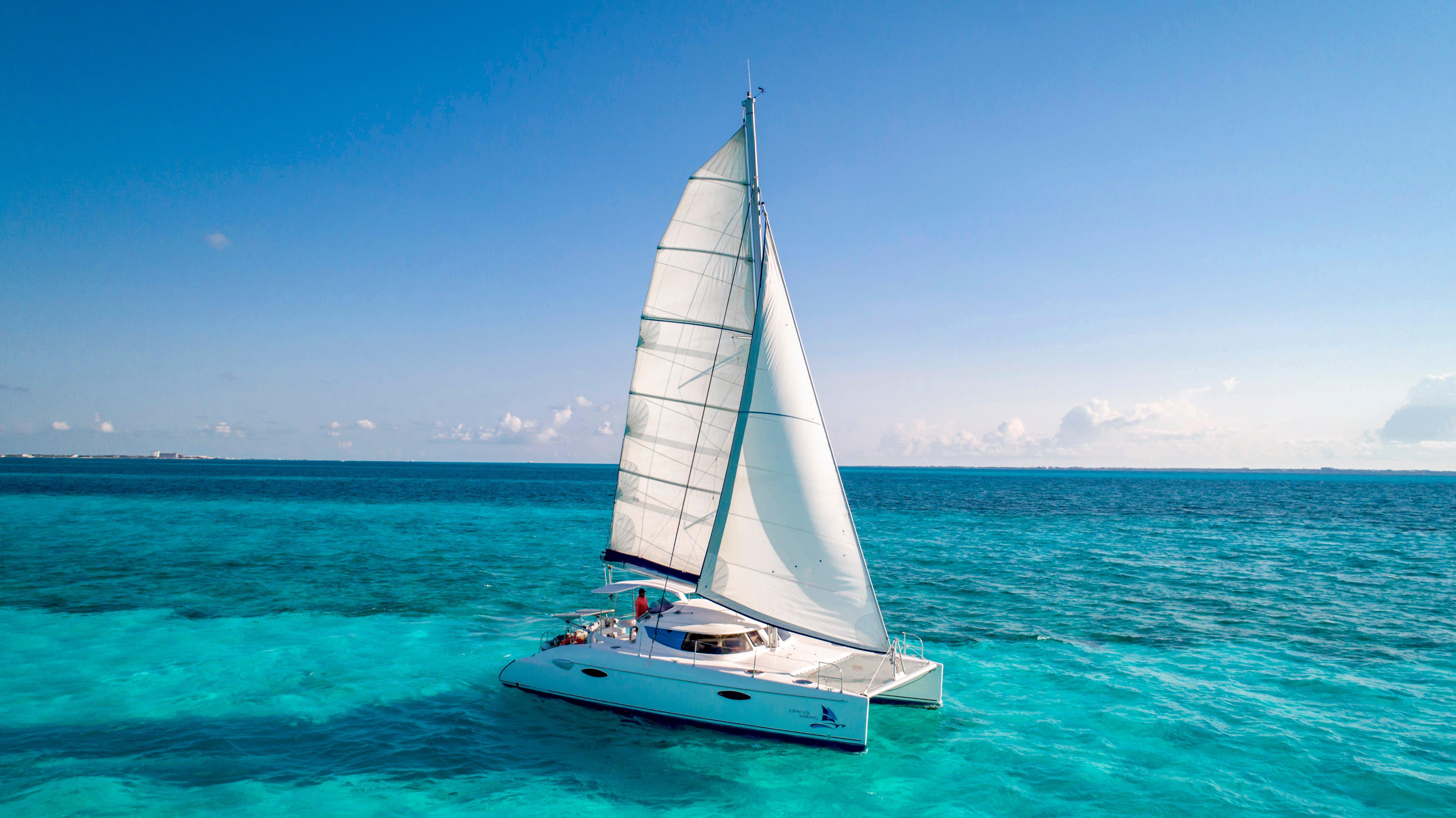 Catamarán con Vela en medio del mar azul y cielo azul